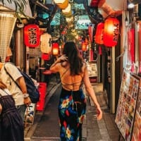 A woman dressed in a colourful dress with open back strolls through a narrow bustling market street of Tokyo. Products are displayed outside shops to tempt passing patrons as they walk underneath chinese laterns