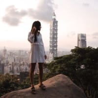 A woman in the foreground poses in front of the Taipei 101 skyscraper, which looms over the city of Taipei, Taiwan